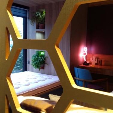 Divisória entre a cama e o armário em MDF trabalhado em hexágonos