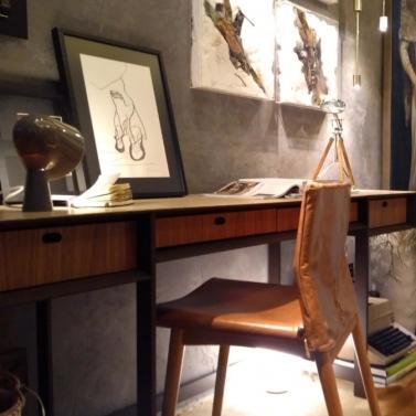 Escrivaninha + cadeira com acabamento em couro + pendente dourado + cimento queimado